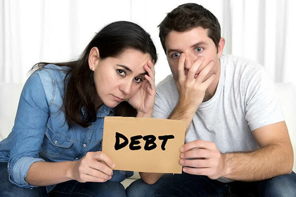 "Stressed out couple with a sign that says ""debt"""